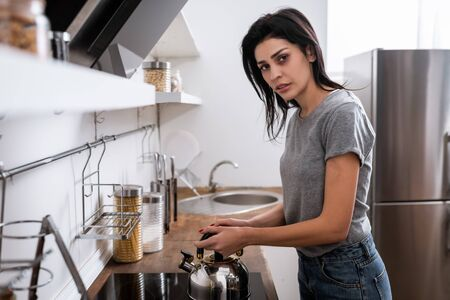 selective focus of woman with bruise on face touching teapot on electric stove in kitchen, domestic violence concept