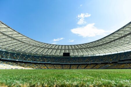 grassy football pitch at stadium at sunny day with blue sky