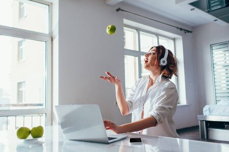 surprised beautiful girl juggling with apples at home with digital devices on quarantine