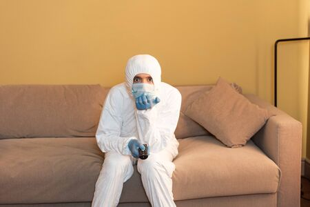 Man in hazmat suit and medical mask clicking channels on couch
