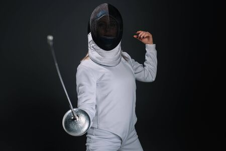Selective focus of fencer holding rapier isolated on black