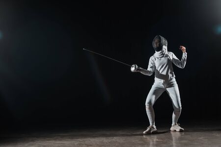 Fencer training with rapier under spotlight on black background Stock Photo