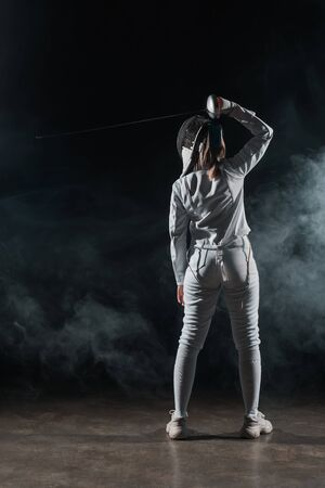 Back view of swordswoman fencing on black background with smoke