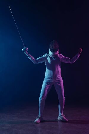 Fencer showing yeah gesture while holding rapier on black background with lighting