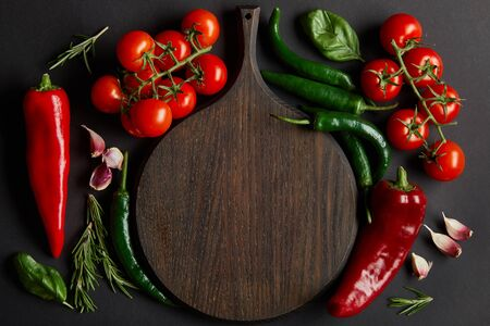 top view of wooden chopping board near ripe cherry tomatoes, garlic cloves, rosemary, basil leaves and green chili peppers on black