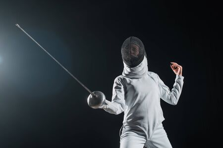 Low angle view of fencer exercising with rapier on black background with lighting