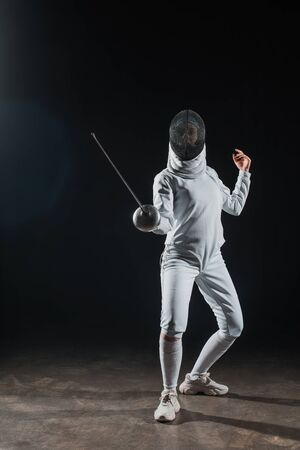 Fencer in fencing mask holding rapier while training under spotlight on black background