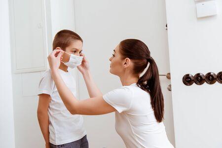 Mother putting on medical mask on son near door in hallway Reklamní fotografie