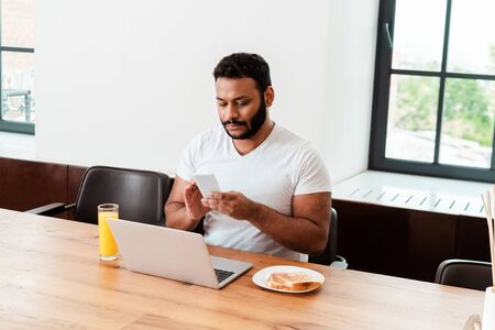african american freelancer looking at smartphone near laptop near breakfast on table Stock Photo
