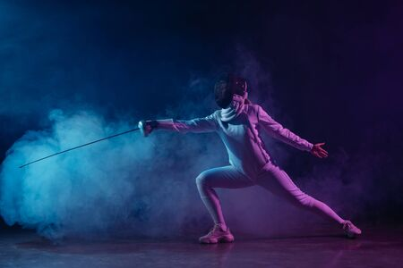 Swordswoman fencing with rapier on black background with smoke and lighting