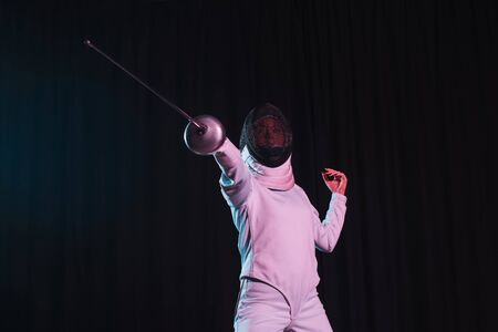 Low angle view of fencer training with rapier isolated on black