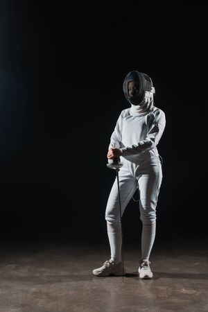 Fencer in fencing mask and suit holding rapier on black background