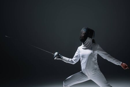 Fencer in fencing mask exercising on black background