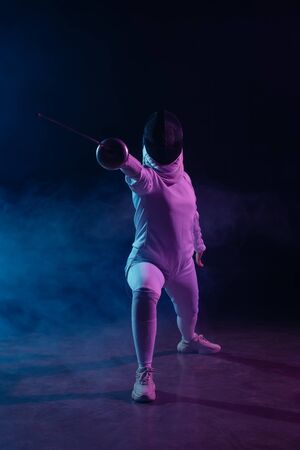 Fencer doing lunge while training with rapier on black background with smoke and lighting