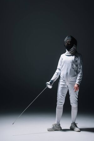 Fencer in fencing mask holding rapier while standing on white surface on black background