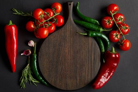 top view of wooden cutting board near ripe cherry tomatoes, garlic cloves, rosemary and green chili peppers on black