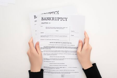 partial view of woman holding bankruptcy papers on white background