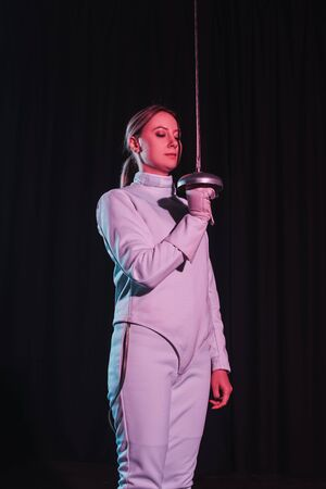 Beautiful woman in fencing suit holding rapier isolated on black