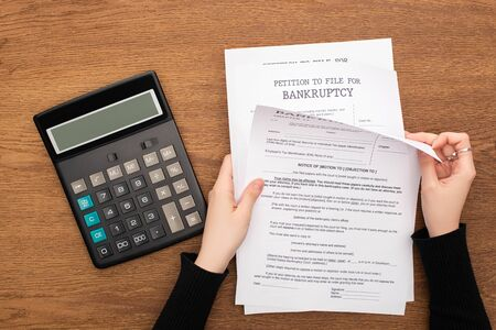 cropped view of woman with bankruptcy papers near calculator on wooden background