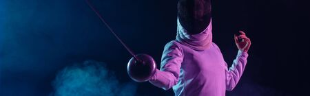 Panoramic crop of swordswoman fencing on black background with smoke and lighting
