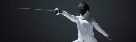 Panoramic shot of fencer in fencing suit and mask exercising isolated on black