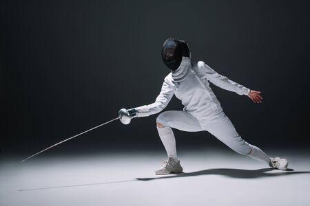 Fencer training under spotlight on black background