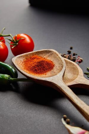 selective focus of organic cherry tomatoes, peppercorns, wooden spoons with paprika powder and green chili peppers on black