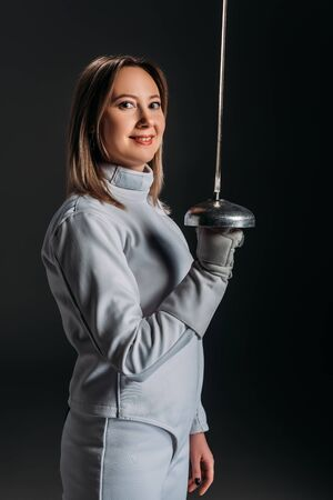 Side view of beautiful fencer smiling at camera while holding rapier isolated on black