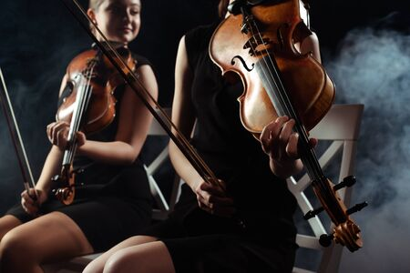 cropped view of attractive musicians playing on violins on dark stage with smoke 版權商用圖片