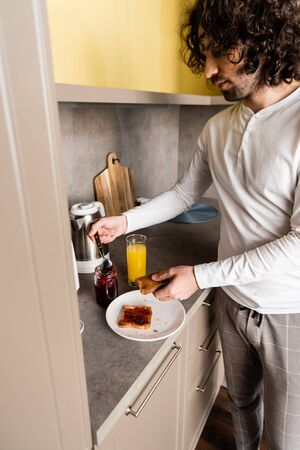 curly young man in pajamas spreading jam on toast for breakfast