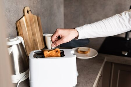 partial view of man taking bread out of toaster in kitchen