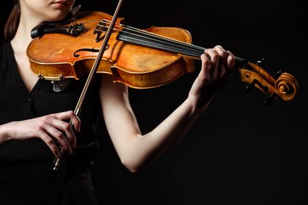 partial view of female musician playing symphony on violin isolated on black Standard-Bild