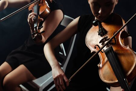 cropped view of professional female musicians playing classical music on violins on dark stage