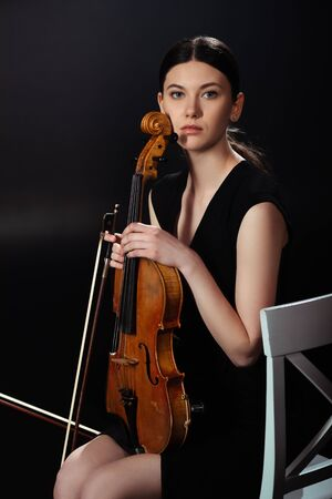 attractive female musician holding violin on dark stage Banque d'images