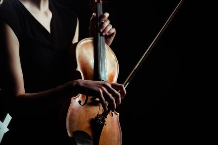 partial view of female musician playing on violin isolated on black