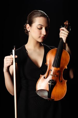 beautiful professional musician holding violin isolated on black