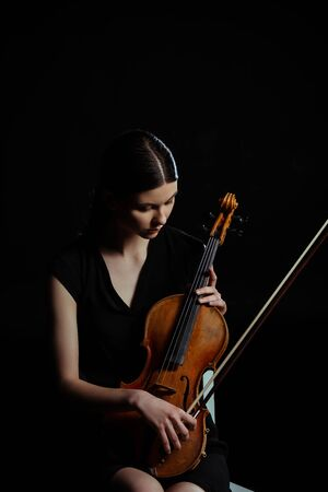 beautiful female musician holding violin isolated on black