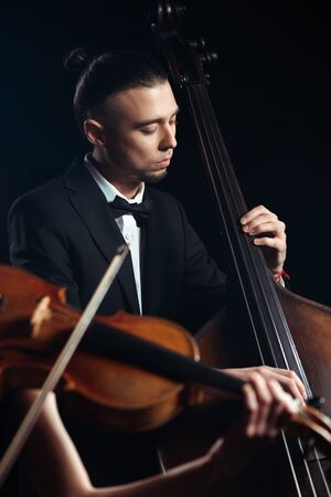 two professional musicians playing on violin and contrabass on dark stage