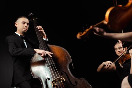 professional musicians playing on double bass and violins isolated on black