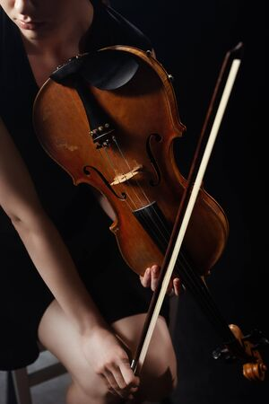 cropped view of professional female musician playing on violin on dark stage