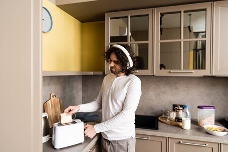 curly man in wireless headphones putting bread into toaster while preparing breakfast