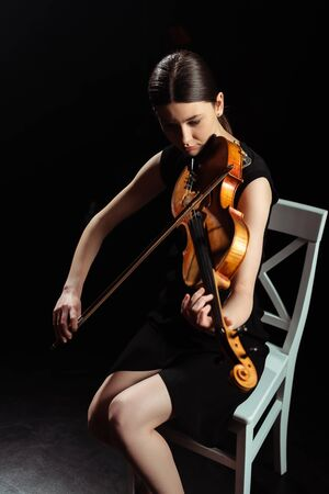 beautiful female musician playing on violin on dark stage Banque d'images