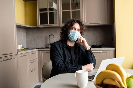 Selective focus of freelancer in medical mask talking on smartphone near laptop, fruits and cup on kitchen table