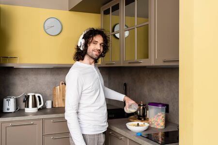 smiling man in wireless headphones pouring milk into bowl with flakes while looking at camera Zdjęcie Seryjne