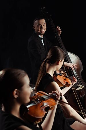 happy professional musicians playing on double bass and violins isolated on black Stock fotó