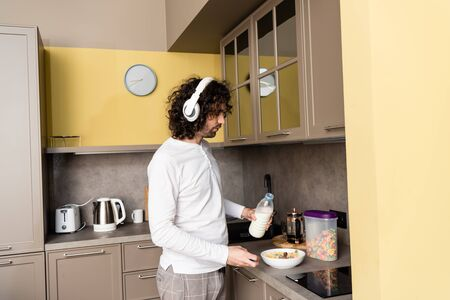 young man in pajamas and wireless headphones pouring milk into bowl with flakes while preparing breakfast