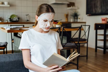 Selective focus of young woman in face mask reading book at home 免版税图像