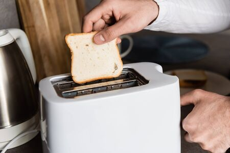 cropped view of man putting piece of bread into toaster