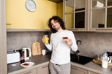 happy man in pajamas holding orange juice and toast with jam while smiling at camera