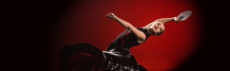 panoramic shot of young flamenco dancer in dress holding fan while dancing on red